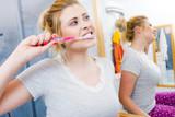 Woman brushing cleaning teeth in bathroom - 242625387