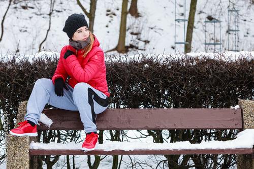 Woman wearing sportswear sitting outside during winter