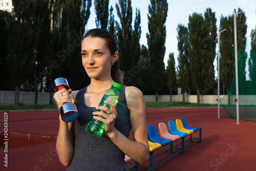 Poster Young sporty woman holding the dumbbell and a water bottle at the stadium. Space for text