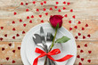 Leinwanddruck Bild - valentines day and romantic dinner concept - close up of red rose flower on set of dishes with cutlery and hearts on wooden table
