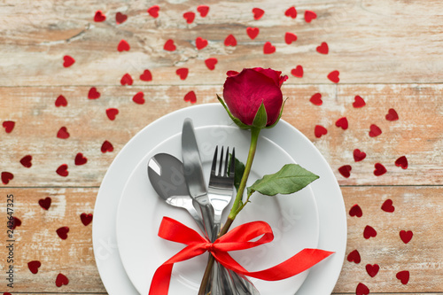 Leinwanddruck Bild valentines day and romantic dinner concept - close up of red rose flower on set of dishes with cutlery and hearts on wooden table