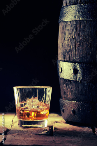 Glass of scotch on the rocks and an old oak barrel