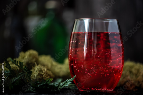 Red grape cocktail with soda on a green background.