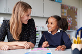Young female primary school teacher working one on one with a schoolgirl at a table in a classroom, both looking at each other smiling, close up - 242654365