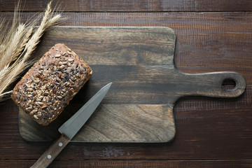 Loaf of fitness rye bread with ears of wheat on wooden board. Space for text.
