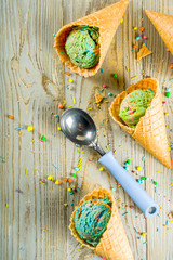 Multicolored rainbow ice cream with icecream cones on wooden background