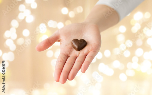 obraz lub plakat valentines day, sweets and confectionery concept - close up of hand holding heart shaped chocolate candy over festive lights on beige background