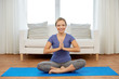 Leinwanddruck Bild - mindfulness, spirituality and healthy lifestyle concept - woman meditating in lotus pose at home
