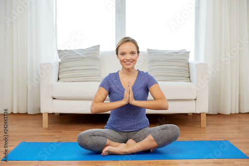 Leinwanddruck Bild mindfulness, spirituality and healthy lifestyle concept - woman meditating in lotus pose at home