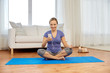 Leinwanddruck Bild - fitness, technology and healthy lifestyle concept - woman with smartphone and earphones doing yoga at home