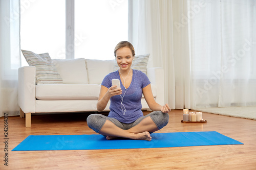 Leinwanddruck Bild fitness, technology and healthy lifestyle concept - woman with smartphone and earphones doing yoga at home