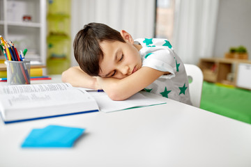 education, childhood and school concept - tired student boy sleeping on table at home