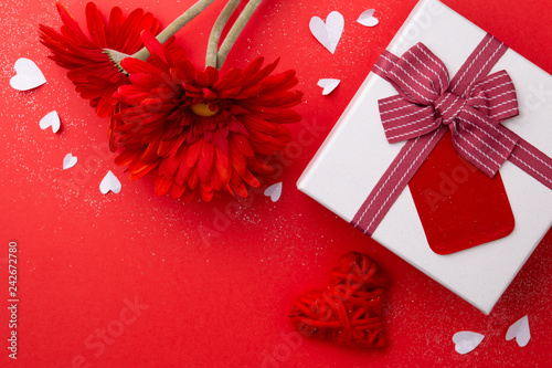 Foto Murales Gift, red gerberas and a heart on a red background.
