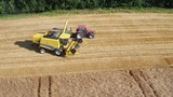 Aerial of a yellow combine harvester in a beautiful golden wheat field as it harvests on a bright sunny day in bavaria germany - 242672984