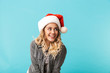 Cheerful girl wearing christmas hat standing