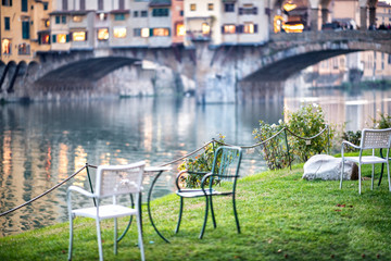 Chairs in Florence Lungarni, Ponte Vecchio on background