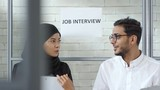 Tracking shot of cheerful Muslim woman in hijab and Arab man in glasses chatting while waiting for job interview - 242691121