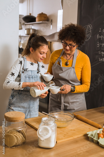 grandmother with her granddaughter baking in kitchen