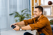 Quadro happy man in glasses playing video game at home