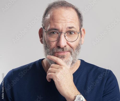 Leinwandbild Motiv Portrait of a bearded mature adult casual Businessman looking into