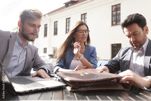 business partners sit at a table on the street,
