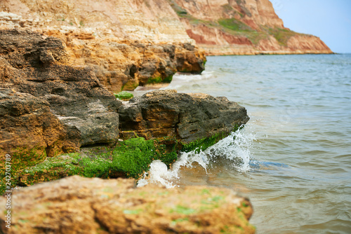 beautiful sea landscape, closeup of stone on the beach, sea coast with high hills, wild nature