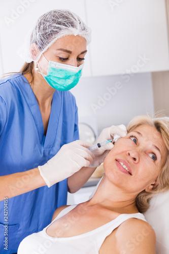 Leinwanddruck Bild Mature female receiving cosmetic injection