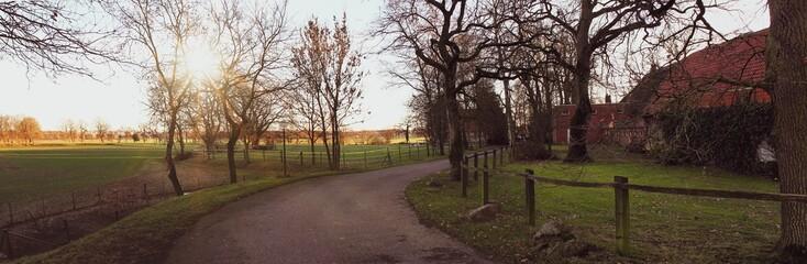 Panorama-Ansicht einer winterlichen Landschaft in Niedersachsen, Deutschland,  Landstraße zwischen Feldern und traditionellen Bauernhäusern © Zitzke
