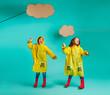 Quadro Cute twins girls dancing in raincoats
