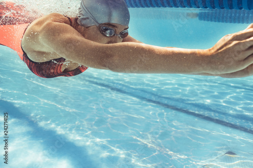 Female swimmer gliding in pool