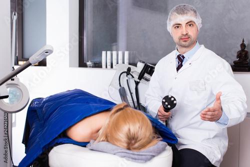 Leinwanddruck Bild Skilled cosmetologist explaining cosmetic procedure using new equipment in clinic