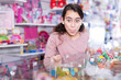 happy schoolgirl delighted with choosing lollipop in store