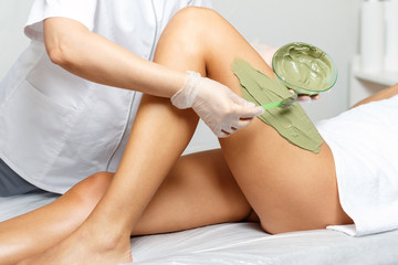 Cosmetologist applies seaweed mud on a woman's hip in medical beauty salon