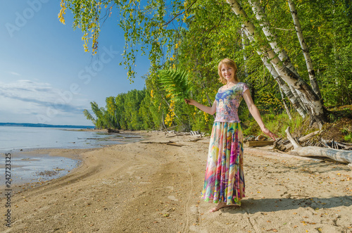 A woman in a bright outfit, in a colorful skirt joyful among the birches on the river Bank, the sea.