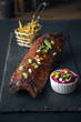 A beautiful delicious golden rack of meaty bbq pork ribs, french fries in a metal frying basket, , and chilli and salad, served on a fashionable grey slate in a dark photography environment.