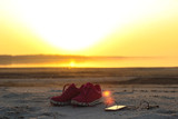 Sports set. Pink sneakers and a mobile phone with headphones close-up on a sandy beach by the sea during sunset..