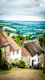 Gold Hill in Shaftesbury is an authentic place in the South of the UK. View of a stone old road on a hill with old English limestone houses with thatched roofs in the background in Dorset countryside. - 242737783