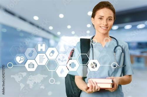 Leinwanddruck Bild Attractive young female medical student with backpack and books