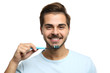 Leinwanddruck Bild - Portrait of young man with toothbrush on white background