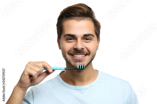 Leinwanddruck Bild Portrait of young man with toothbrush on white background