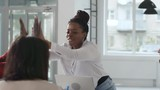 Tracking shot of happy black businesswoman giving high-five to colleagues sitting at table in meeting room - 242762139