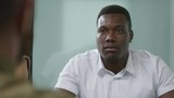 PAN shot of black businessman in casual white shirt discussing work with unrecognizable colleagues during meeting - 242762304