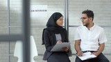 Tracking shot of Muslim woman in hijab and Arab man in glasses holding clipboards and chatting while waiting for job interview - 242762776