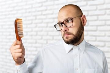 Adult bald  man hand holding comb