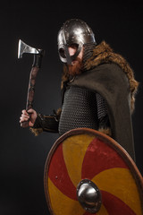 Warrior Viking in full arms with axe and shield on dark background © Fotokvadrat