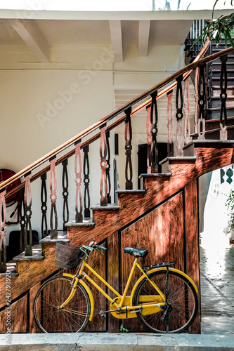 bicycle near the steps, old yellow bicycle wooden background