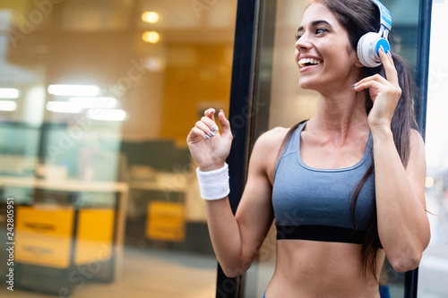 Leinwanddruck Bild Portrait of happy fit woman in city. Healthy lifestyle concept