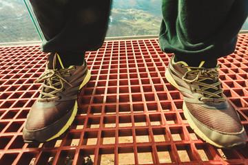 Tourist feet on Dalsnibba platform floor, Norway