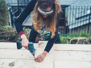 Woman using impact driver outdoors