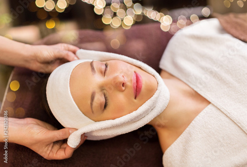 Leinwanddruck Bild people, beauty, lifestyle and relaxation concept - beautiful young woman lying with closed eyes and having face massage with towel at spa